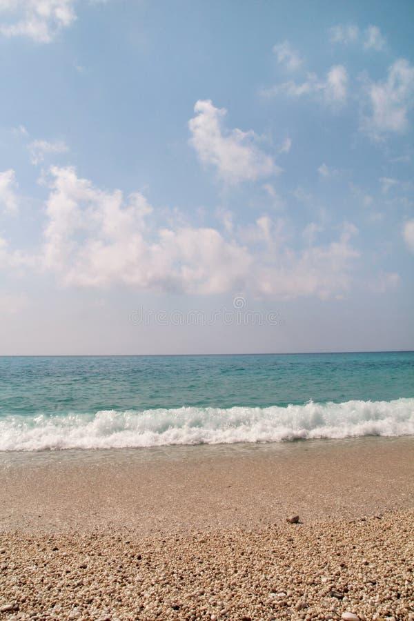 异乎寻常的沙滩、热带地中海有波浪和海泡沫的,天空蔚蓝和云彩 自然环境,风景 免版税库存照片