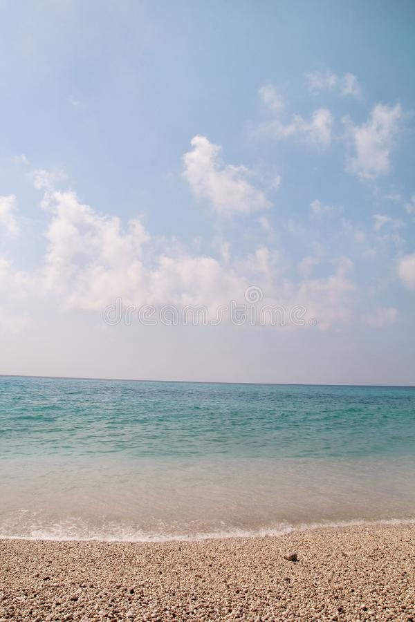 异乎寻常的沙滩、热带地中海有波浪和海泡沫的,天空蔚蓝和云彩 自然环境,风景 库存照片