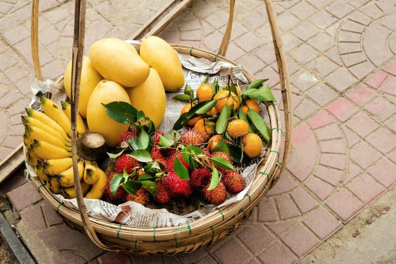 异乎寻常的热带水果芒果,香蕉,蜜桔,在篮子的红毛丹 库存图片