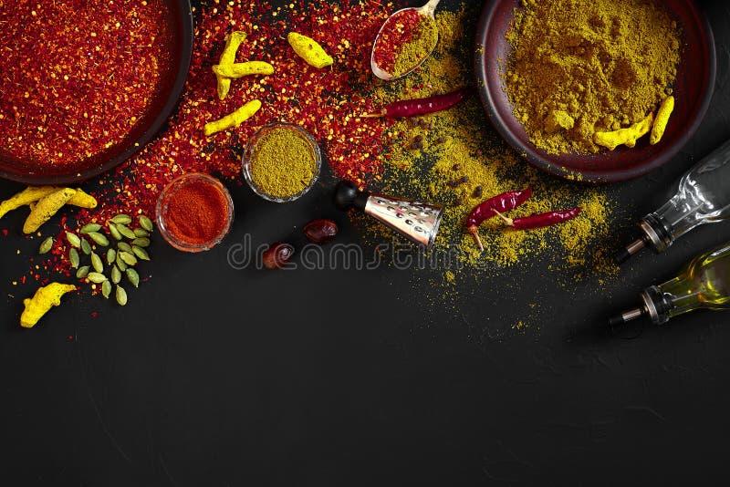 异乎寻常香料混合-香料,草本,搽粉在黑暗的背景的顶视图 烹调和辣食物概念 复制空间 免版税库存照片