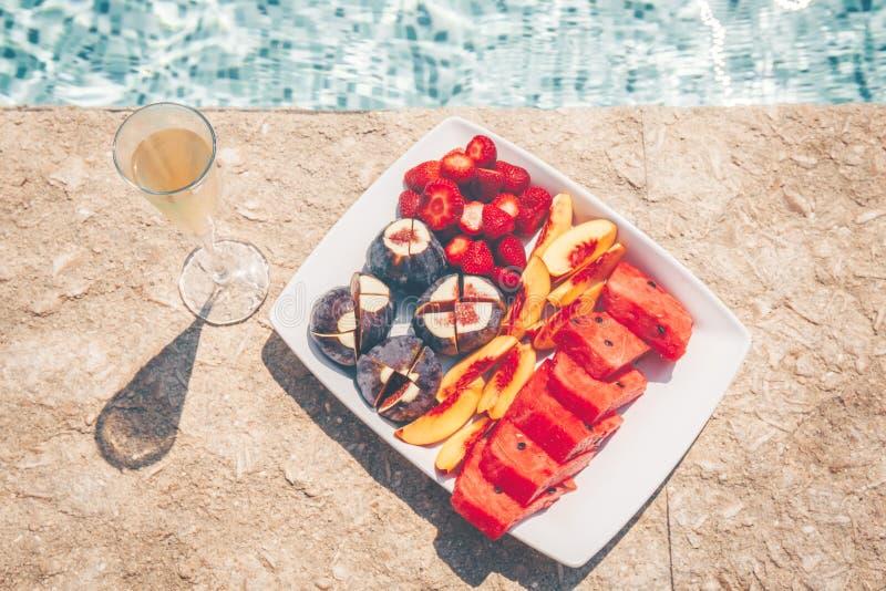异国情调的热带水果盘和泳池边的香槟 库存图片