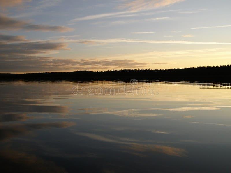 异常的云彩在河反射了在日落以后 免版税库存照片