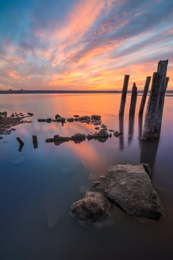 异常的柱子在五颜六色的天空背景的水中  免版税图库摄影