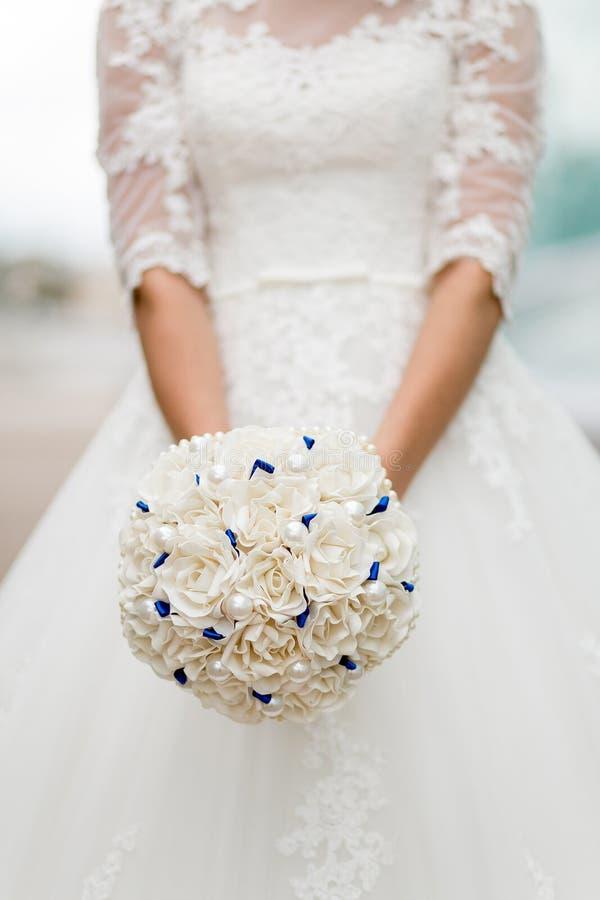 异常的软的白色婚礼花束在新娘的手上 免版税库存图片