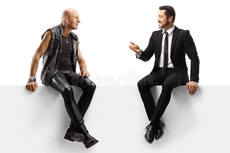 弃踢手和一个商人坐在面板上,聊天 免版税库存照片