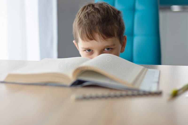 弄翻8岁做他的家庭作业的男孩在桌上 免版税图库摄影