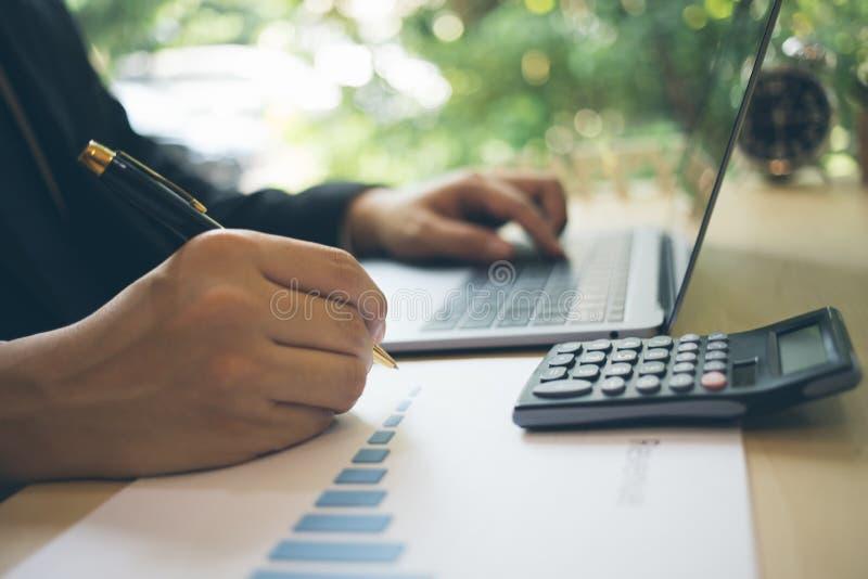 弄脏在图表纸的商人文字在工作站 在图表纸和使用膝上型计算机的现代商人文字 免版税库存图片