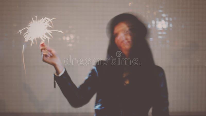 弄脏在少妇跳舞的行动图象与灼烧的闪烁发光物的在她的在夜城市街道的手上,减速火箭的颜色 免版税库存照片