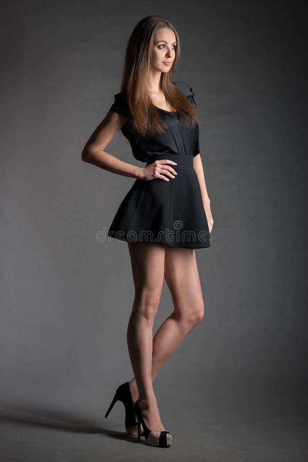 年轻式样妇女画象黑短裙和长的腿的 库存图片