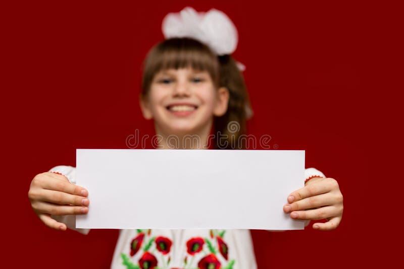 弓举行白色白纸的逗人喜爱的微笑的小女孩 图库摄影