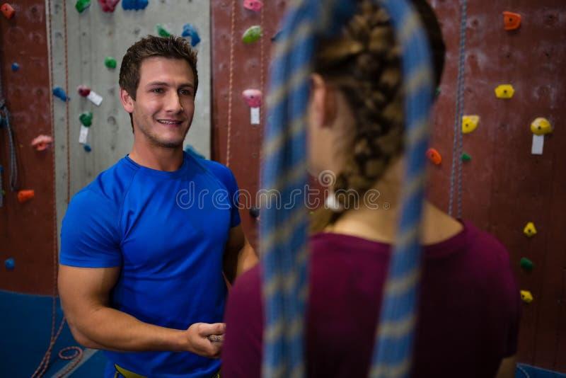 引导女运动员的微笑的教练员在墙壁上升 库存图片