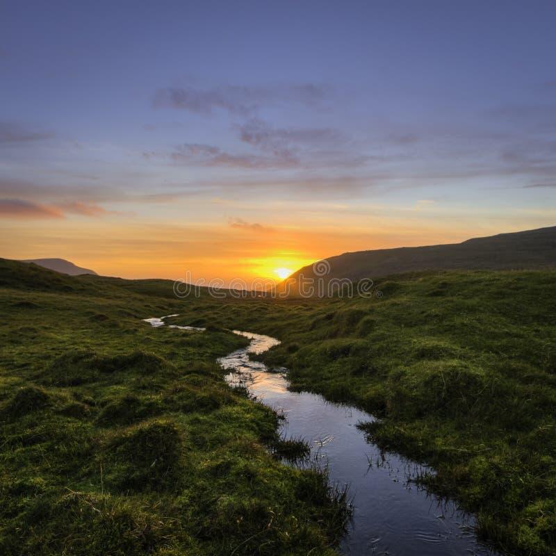 引导方式的小河对与红色云彩和蓝天的日落 (法罗岛) 免版税库存图片