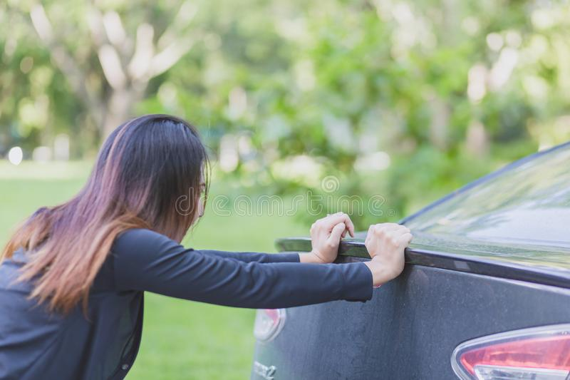 引擎划分 推挤一辆肮脏的汽车的坚强的妇女 运输,配合,概念 库存照片