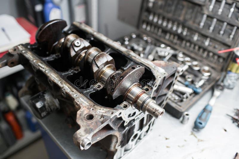 引擎曲轴,阀门盖子,活塞 技工安装工在汽车发动机维护修理工作 库存照片