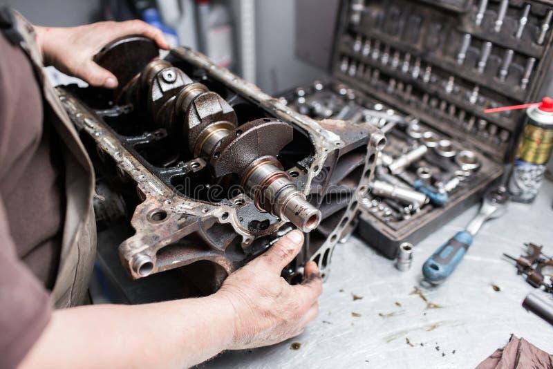 引擎曲轴,阀门盖子,活塞 技工安装工在汽车发动机维护修理工作 免版税图库摄影