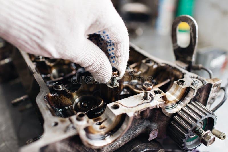 引擎曲轴,阀门盖子,活塞 技工安装工在汽车发动机维护修理工作 免版税库存图片
