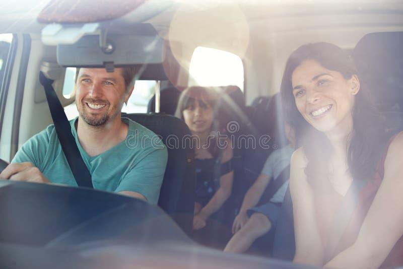 引起在他们的汽车的一次旅途上的幼小白色四口之家,被看见通过前面挡风玻璃 库存图片