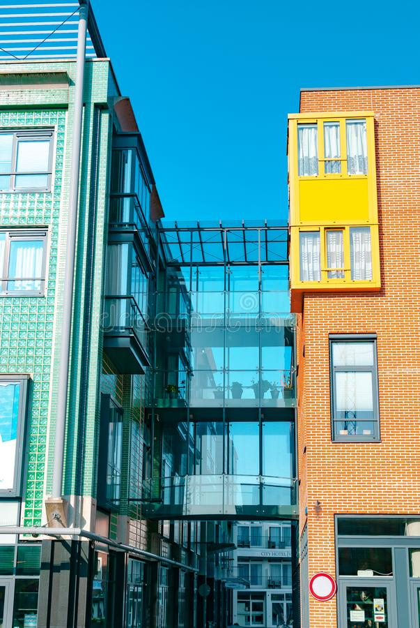 弗利辛恩,荷兰- 2015年4月:现代建筑学 连接两个大厦的玻璃步行桥 中心内部购物中心购物 库存图片