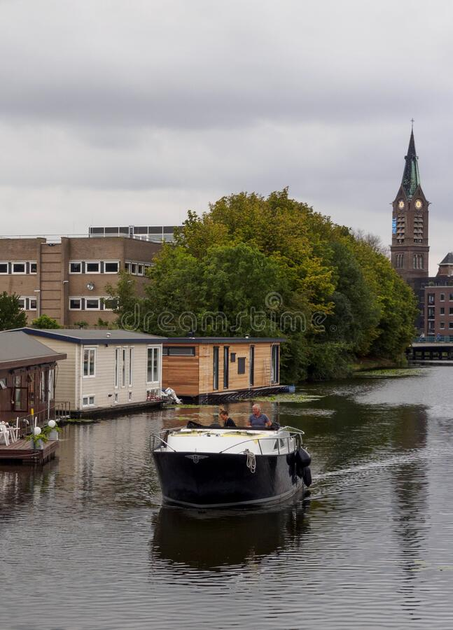 弗拉尔丁根,荷兰鹿特丹 2018年8月:游艇沿着运河航行,水上有传统房屋 图库摄影