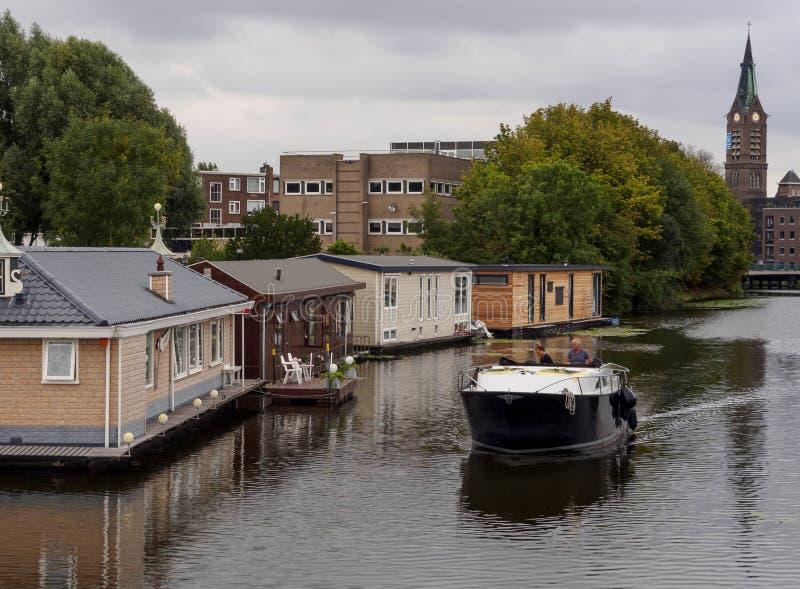 弗拉尔丁根,荷兰鹿特丹 2018年8月:游艇沿着运河航行,水上有传统房屋 库存图片
