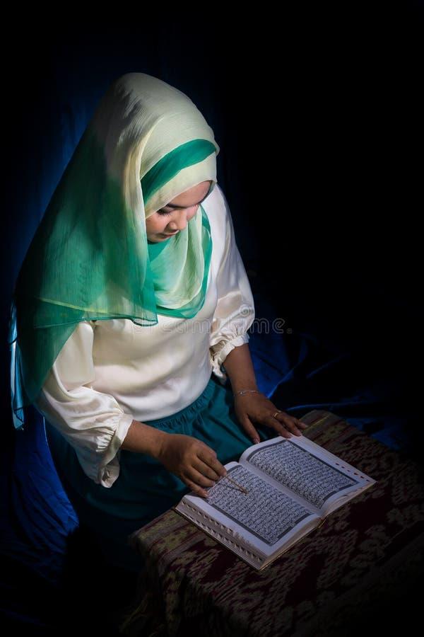 弗洛勒斯,INDONESIA-JUNE 25 2014年:一个十几岁的女孩大约佩带hijab的15-20岁在与种族的一张桌读古兰经 免版税库存图片