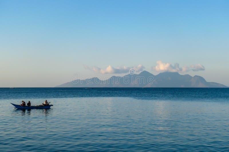 弗洛雷斯/印度尼西亚20290808:一艘渔船在印尼莫梅雷附近的平静海面上穿过,一艘蓝色的小船上有三名男子 库存照片