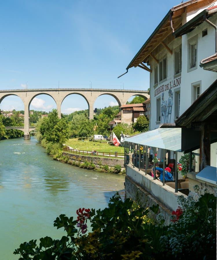 弗里堡,FR/瑞士- 2019年5月30日:河的Saane餐馆在弗里堡有现代Poyabruecke的一个巨大看法 免版税图库摄影