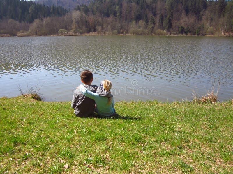 弟弟和姐妹由湖 免版税库存照片