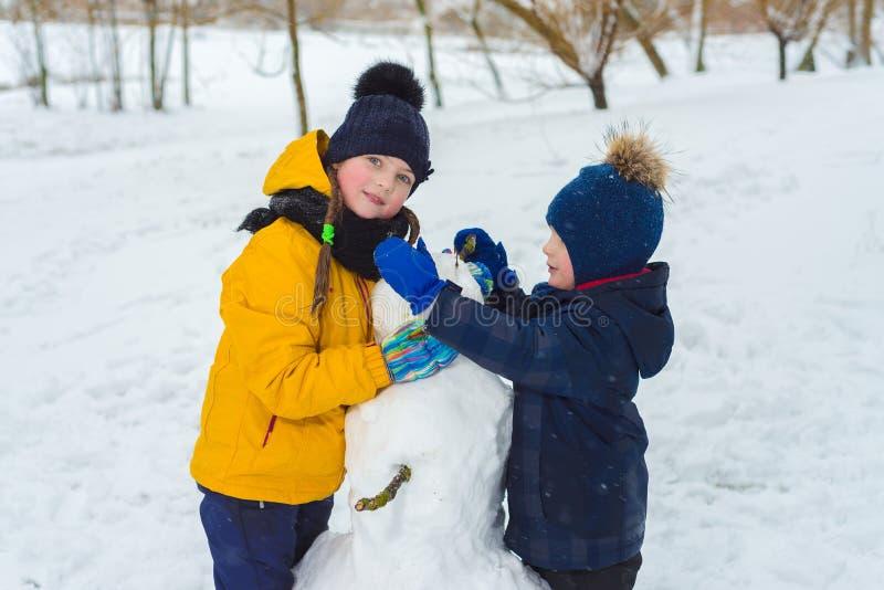 弟弟和姐妹画象  儿童游戏在冬天 免版税库存图片