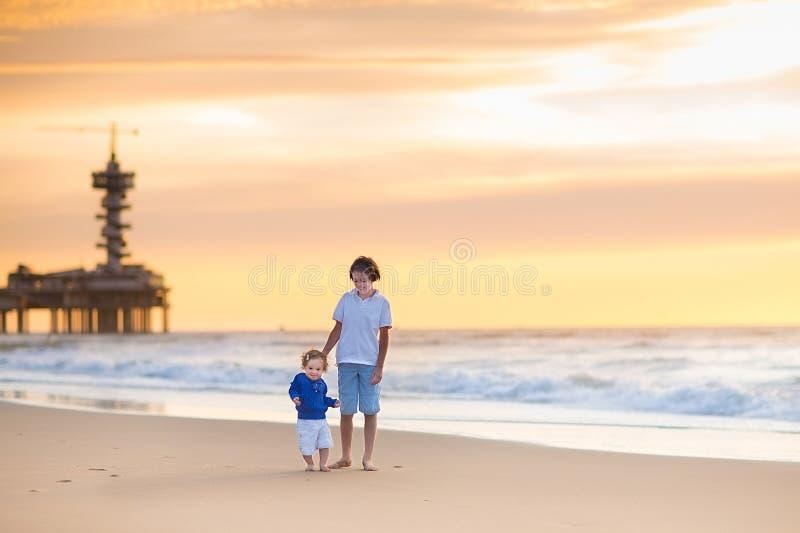 弟弟和他的小姐妹海滩的在日落 图库摄影