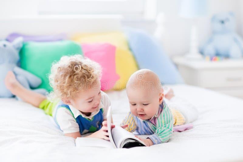 弟弟在床上的读一本书 免版税库存图片
