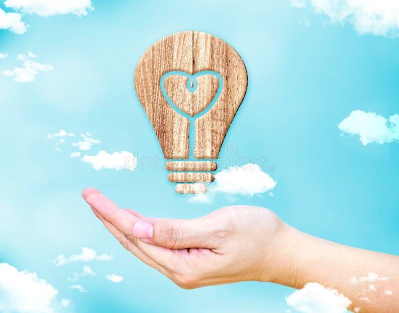 张开有心脏的女性手在与蓝天的电灯泡木象 免版税库存图片