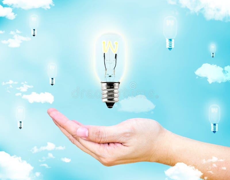 张开有浮动发光的电灯泡的女性手有蓝天的a 库存图片