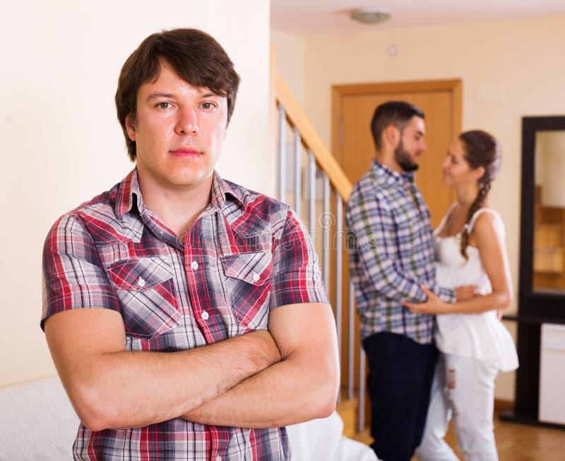紧张的丈夫观看的挥动的配偶 免版税库存照片