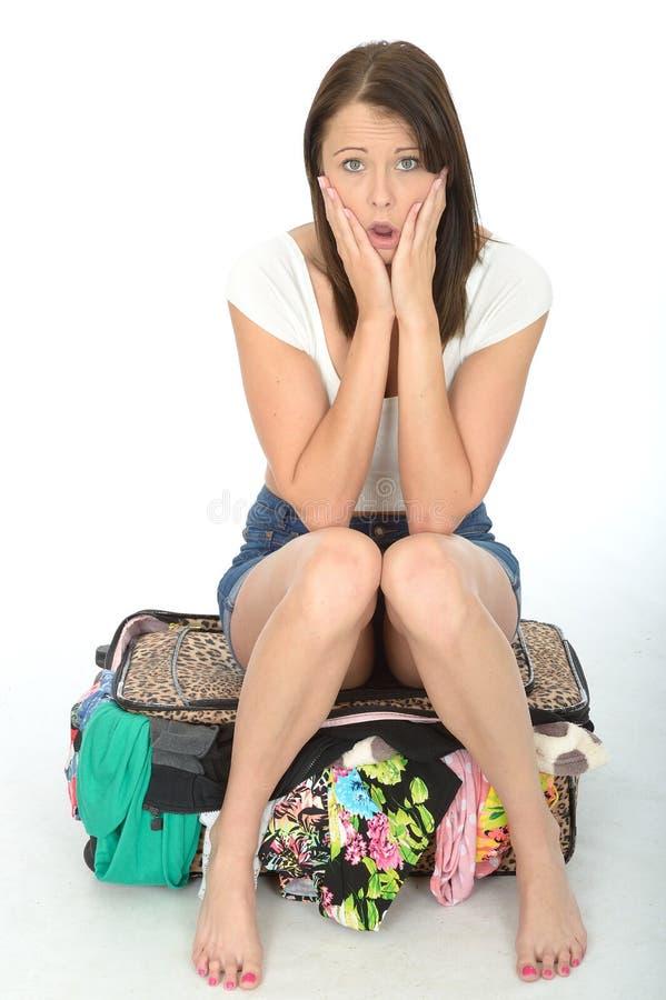 紧张的害怕的急切少妇坐一个溢出的手提箱 库存图片