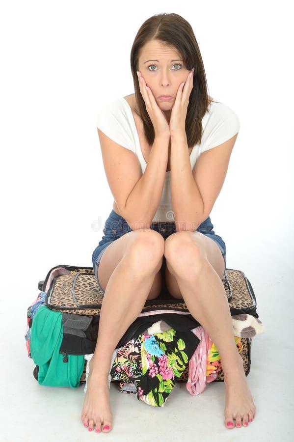 紧张的急切害怕的少妇坐一个溢出的手提箱 库存照片