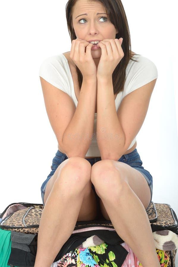 紧张的担心的急切少妇坐一个溢出的手提箱 免版税库存图片