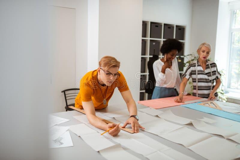 弯曲在书桌的被聚焦的严肃的年轻人 免版税图库摄影