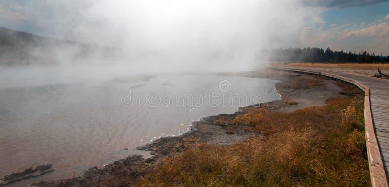 弯曲在热的在更低的喷泉水池的湖温泉附近的木板走道在黄石国家公园在怀俄明美国 免版税库存图片
