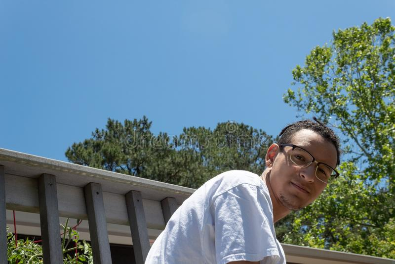 弯曲在看的年轻人照相机,与天空蔚蓝拷贝空间的住宅门廊 免版税库存照片