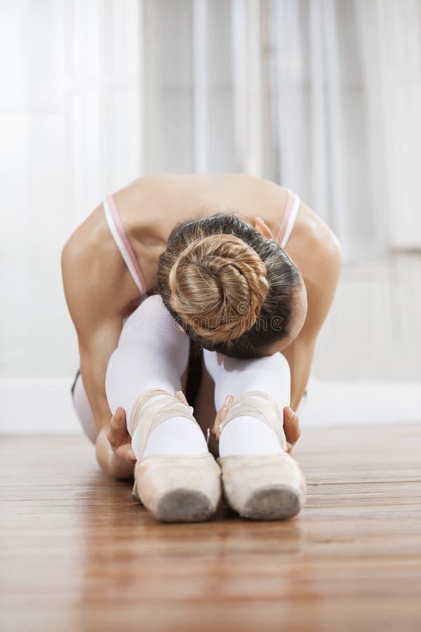 弯曲在硬木地板上的芭蕾舞女演员在演播室 免版税图库摄影