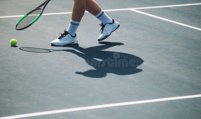 弯曲的网球员采摘球 免版税库存照片