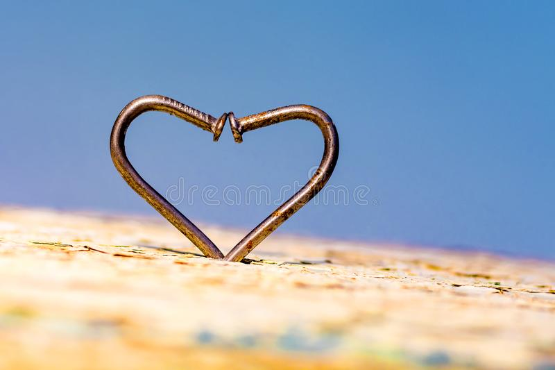 弯曲的钉子的心脏在蓝色背景, overco的标志的 库存照片