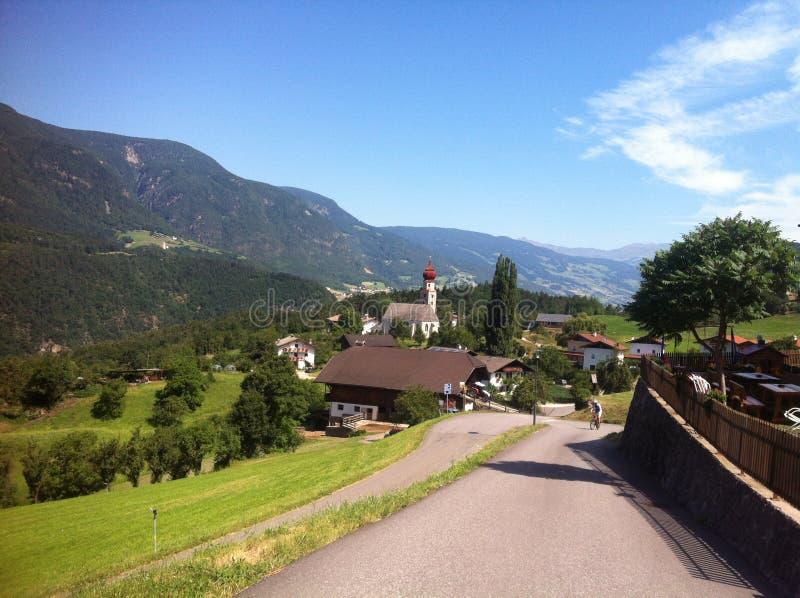 弯曲道路的骑自行车者在Alpe di Siusi,意大利 免版税库存照片