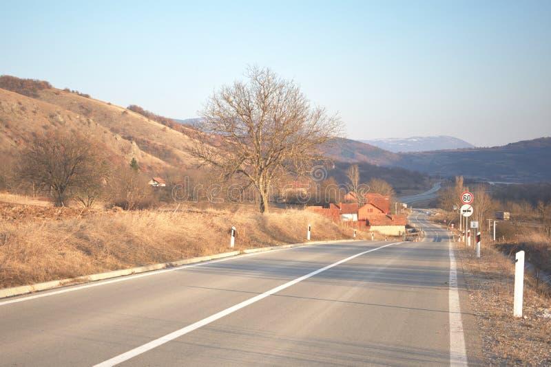 弯曲道路通过小村庄 库存照片