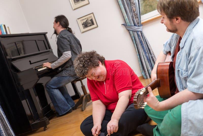 弱智的妇女享受她的音乐疗法 库存图片