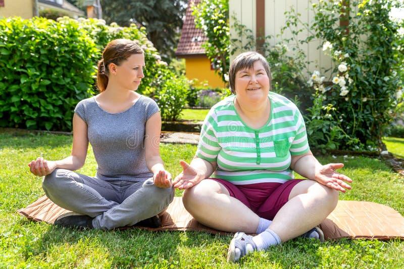 弱智的妇女和教练做着瑜伽锻炼 库存照片