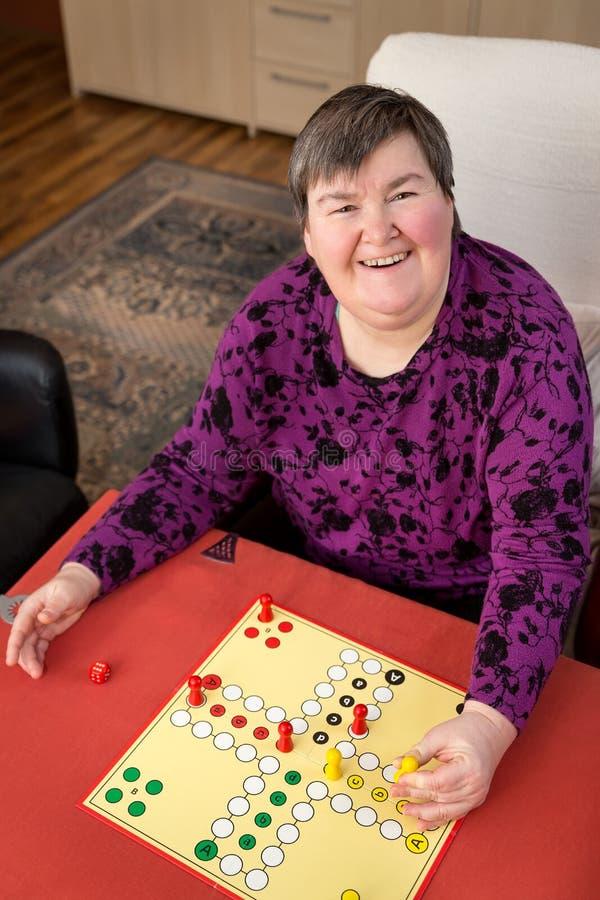 弱智的妇女在家是赌博,每日定期 库存照片
