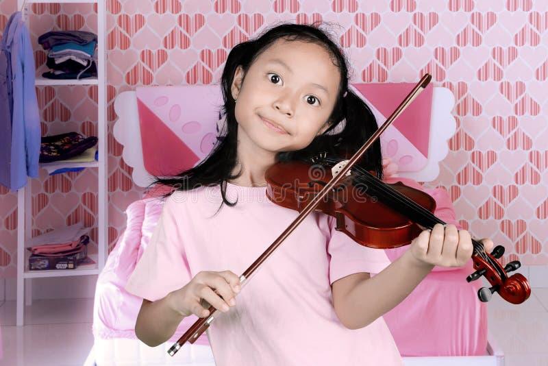 弹一把小提琴的小女孩在卧室 免版税图库摄影