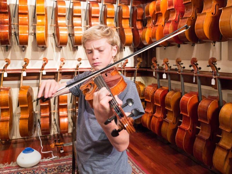 弹一把小提琴的男孩小提琴手在音乐商店 库存图片